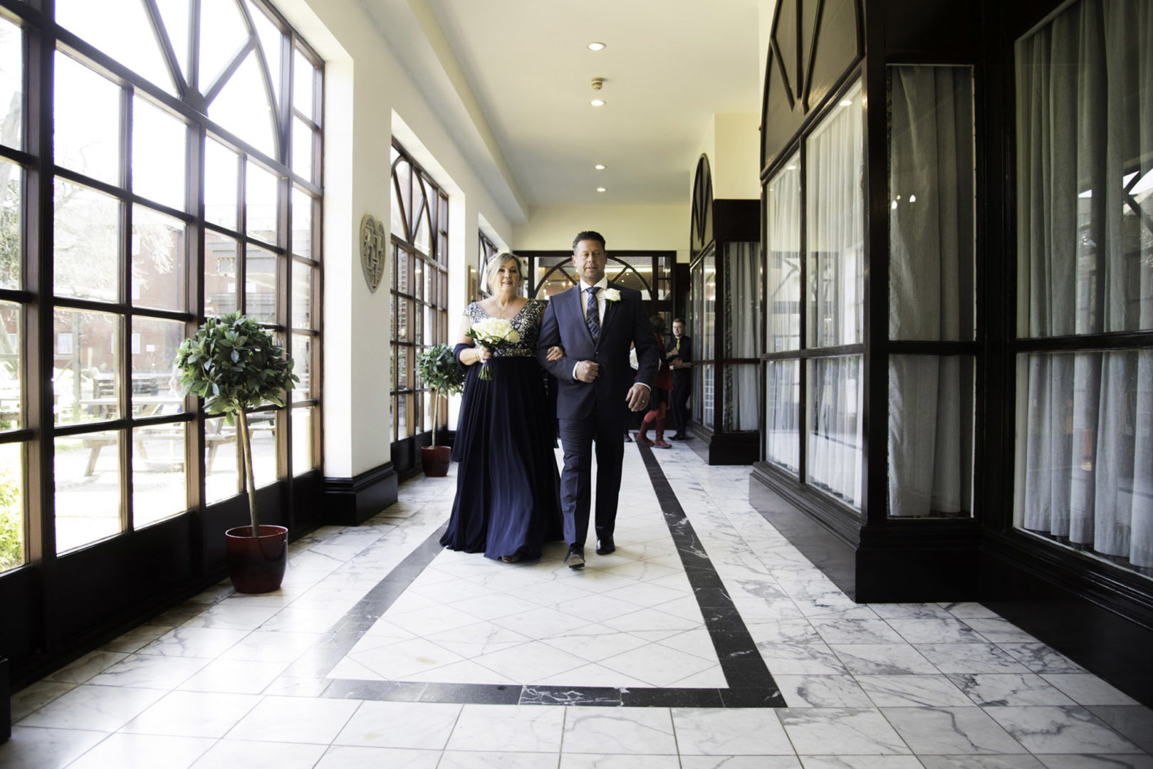 Lynn walks the last few steps accompanied by her son. Photo by AJTImages. Wedding vow renewal at The Royal Court Hotel