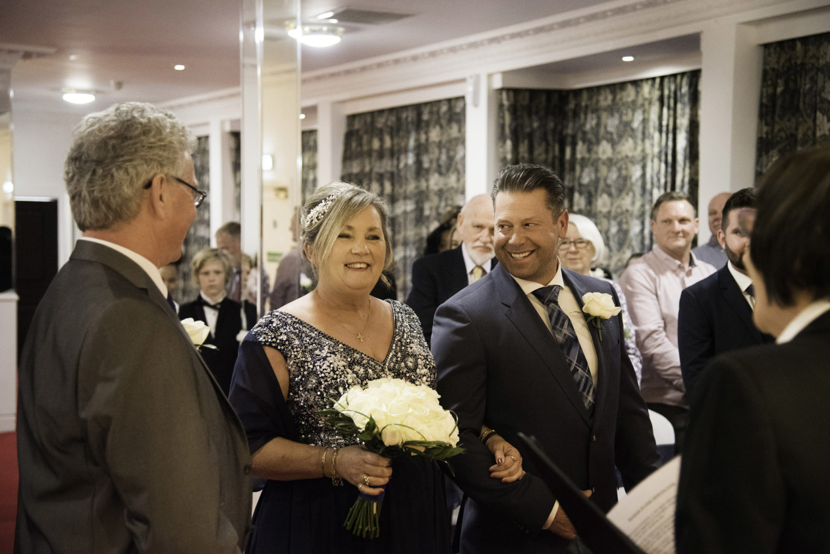 Smiles all round as Lynn stands with Doug ready to renew their vows. Photo by AJTImages. Wedding vow renewal at The Royal Court Hotel