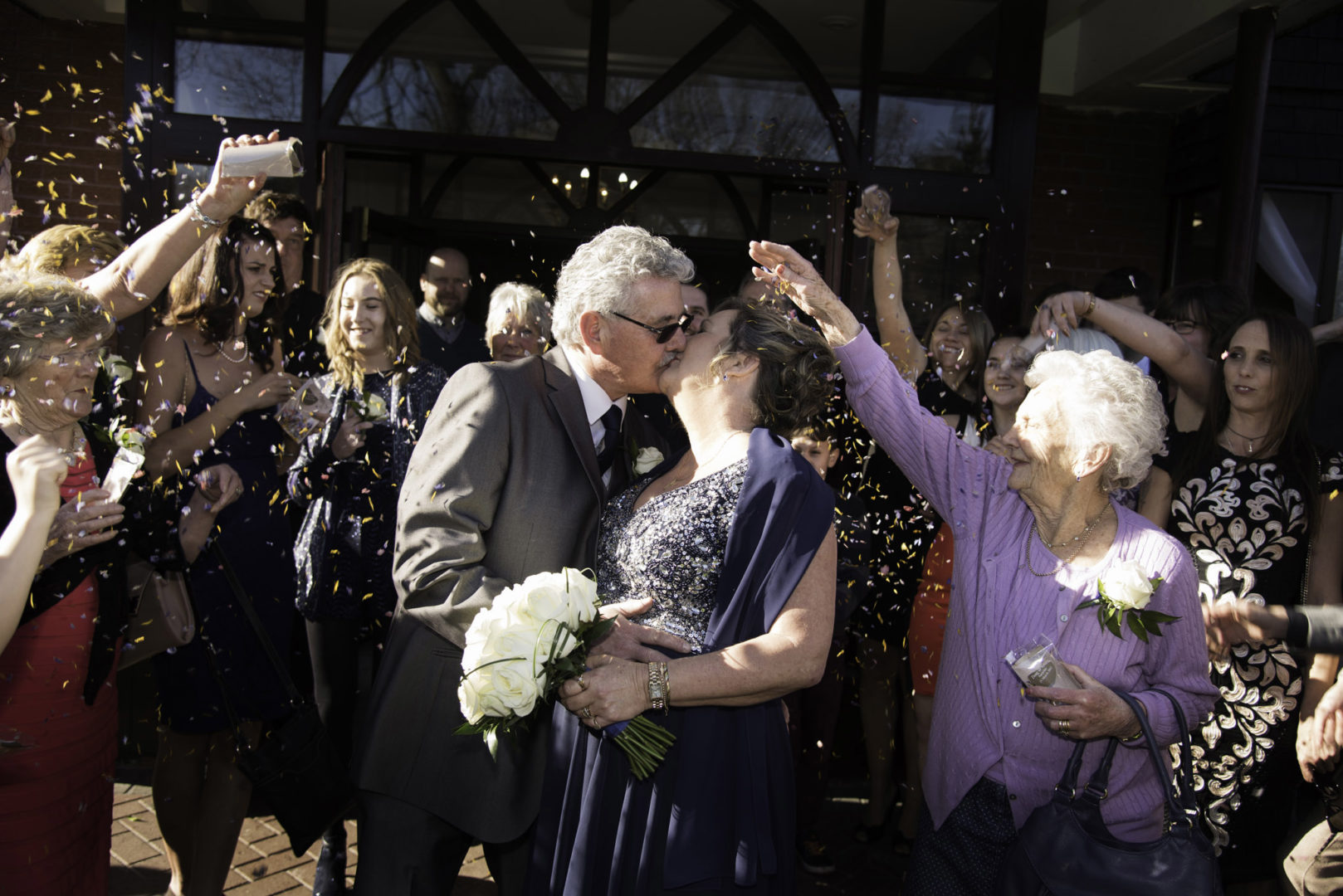 A confetti toss in the sun, beautiful petals rain over Lynn and Doug. Photo by AJTImages. Wedding vow renewal at The Royal Court Hotel