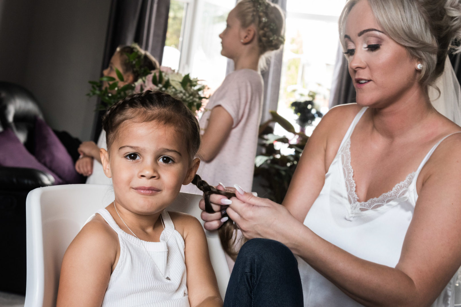 Coventry bride Carrie, helps a flowergirl with her hair.