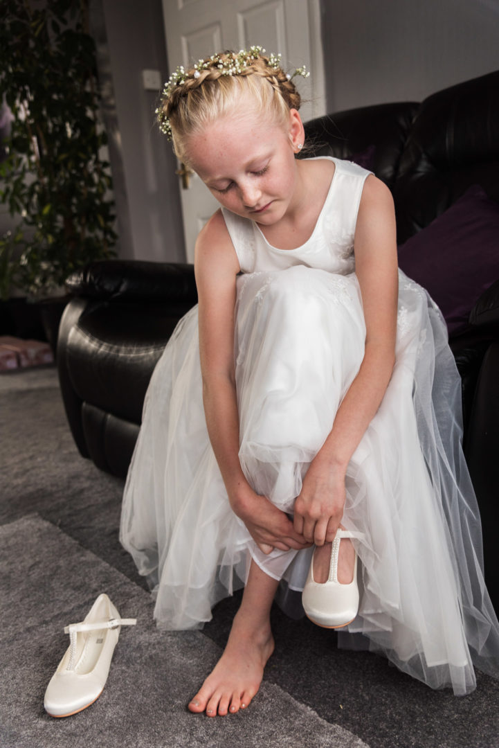 A  Coventry flowergirl is busy putting her shoes on.